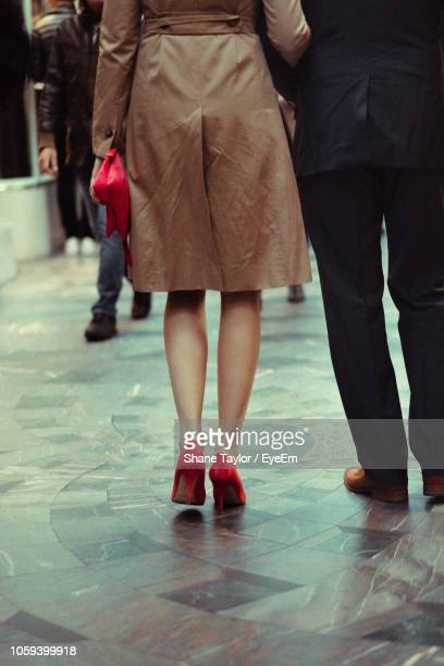 Low Section Of Couple Walking On Footpath In City