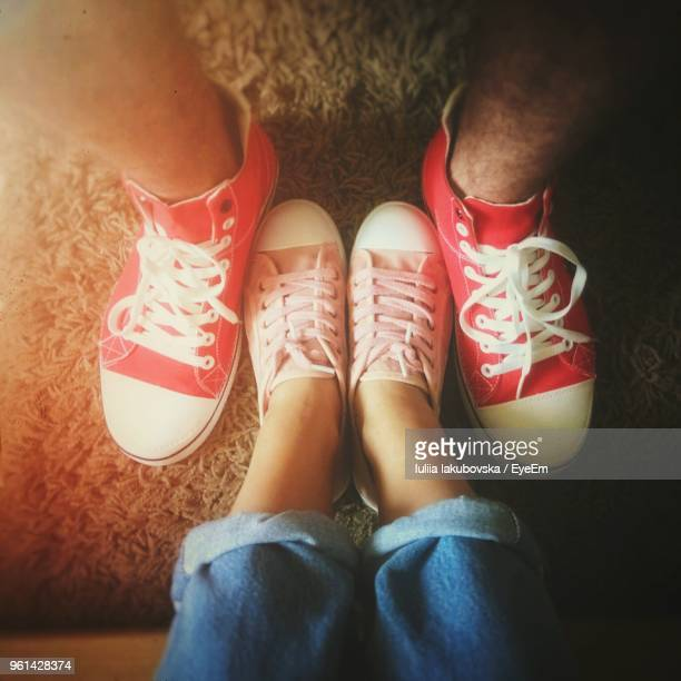 low section of couple wearing canvas shoes on rug - pink pants stock pictures, royalty-free photos & images