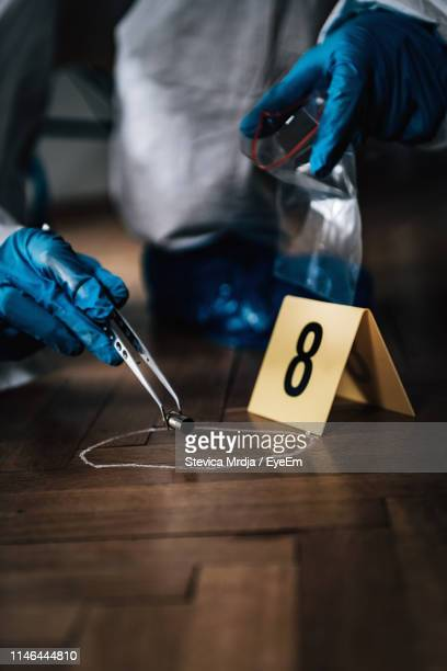 low section of detective looking plastic while crouching at crime scene - crime and murder stock pictures, royalty-free photos & images