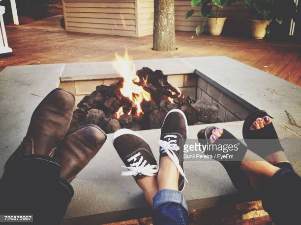 low section of family relaxing by fire pit - fire pit stock pictures, royalty-free photos & images