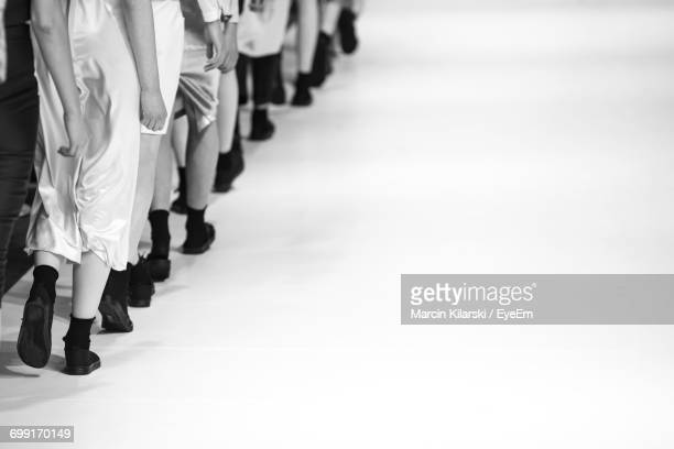 low section of fashion models walking on runway - catwalk stock pictures, royalty-free photos & images
