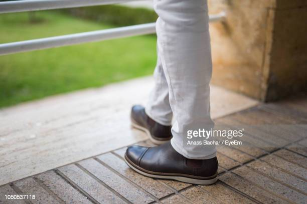 Low Section Of Fashionable Man Wearing Shoes While Standing On Floor