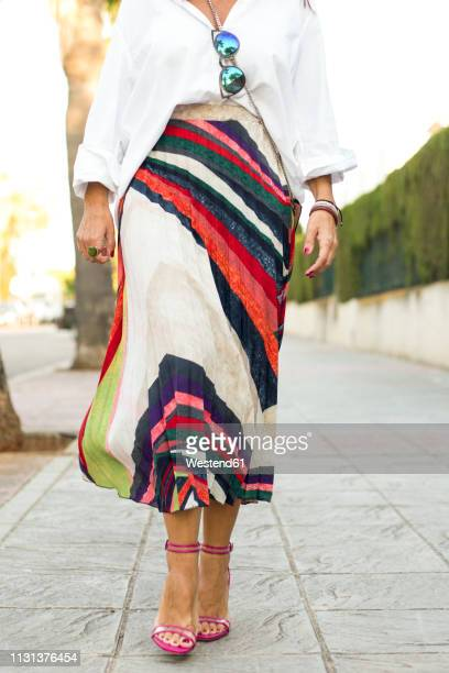 low section of fashionable woman walking on pavement - sandale stock-fotos und bilder
