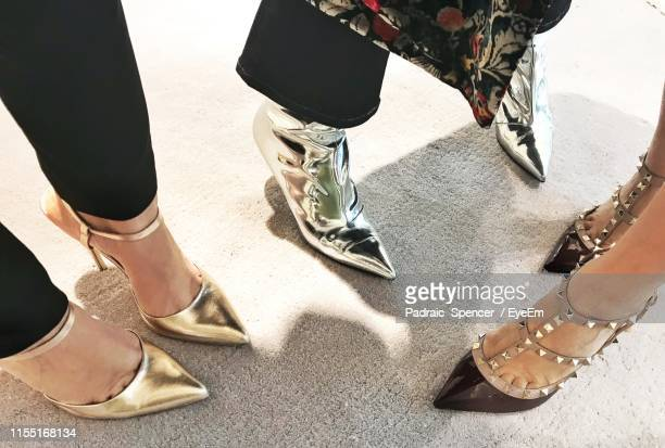 low section of fashionable women wearing modern shoes while standing on street - arab feet photos et images de collection