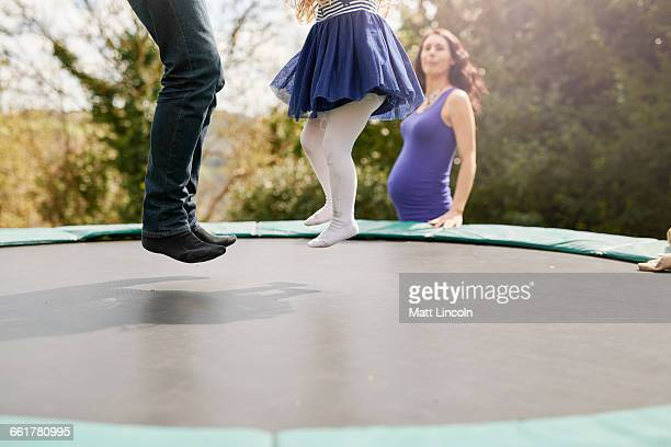 Low section of father and daughter bouncing on trampoline