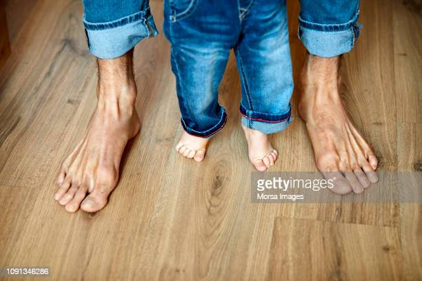 low section of father and son are barefoot - blue trousers stock pictures, royalty-free photos & images