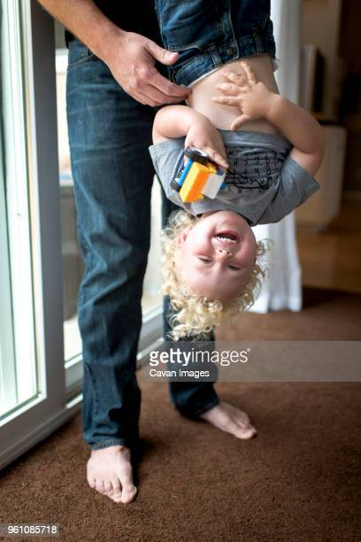 low section of father carrying cheerful son upside down at home - op z'n kop stockfoto's en -beelden