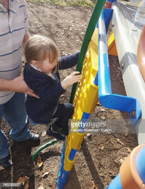 Low Section Of Father Helping Daughter While Climbing On Play Equipment At Park