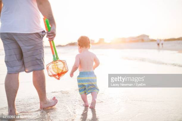 Low Section Of Father With Son On Shore At Beach