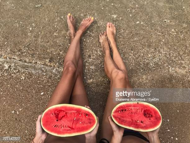 Low Section Of Female Friends Eating Watermelon On Shore At Beach