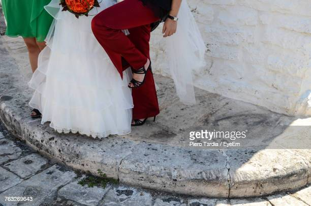 Low Section Of Female Friends With Bride Standing On Footpath