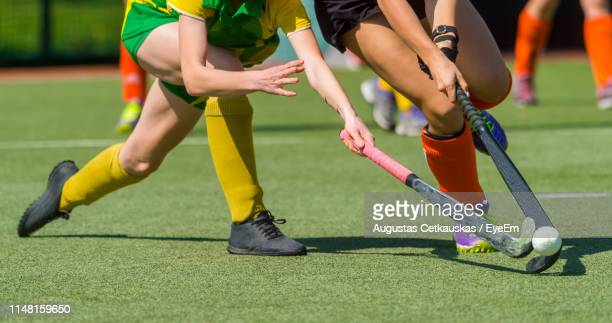 low section of female players playing hockey on field - hockey fotografías e imágenes de stock