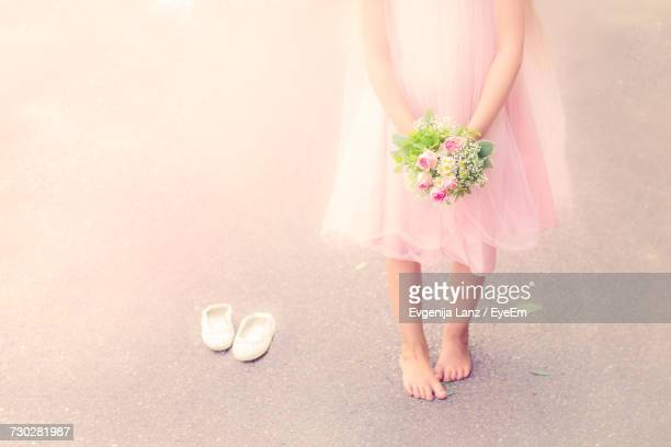 Low Section Of Flower Girl With Bouquet Standing On Footpath