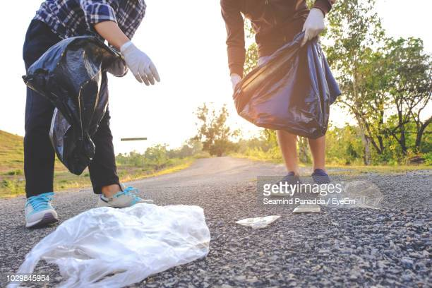 low section of friends collecting garbage on road - city cleaning stock pictures, royalty-free photos & images