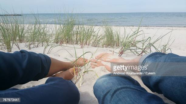 Low Section Of Friends Relaxing At Beach
