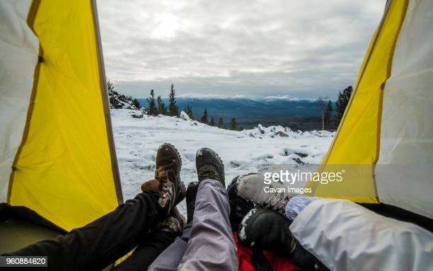 Low section of friends resting in tent on snowcapped mountain