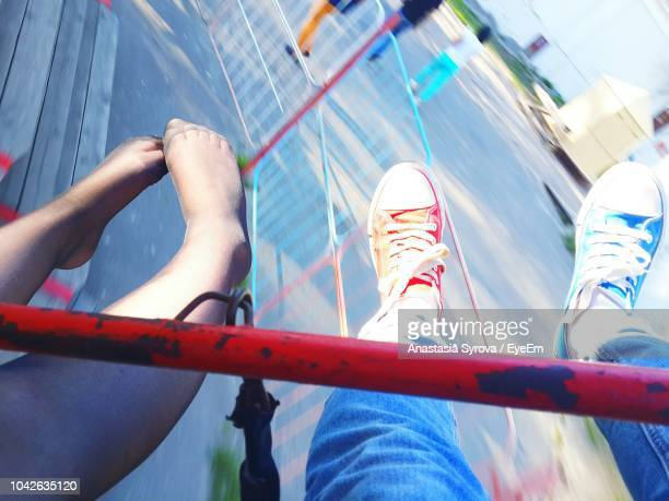 low section of friends sitting on carousel at amusement park - low section stock pictures, royalty-free photos & images