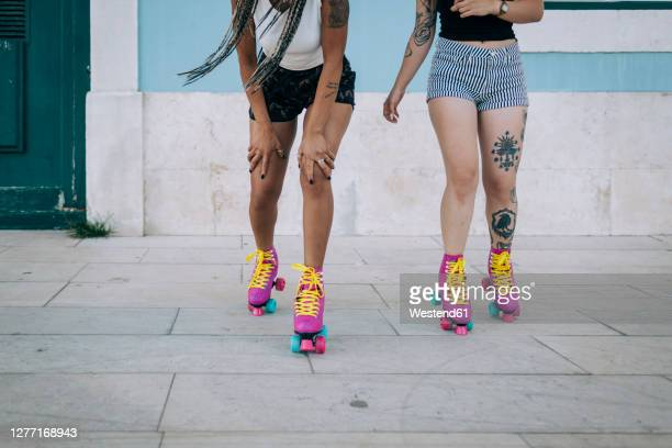 low section of friends skating on footpath against wall in city - roller skating stock pictures, royalty-free photos & images