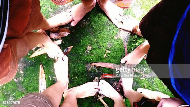Low Section Of Friends Standing On Field And Making Star Shape