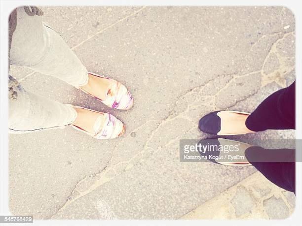low section of friends standing on footpath - sezione inferiore foto e immagini stock