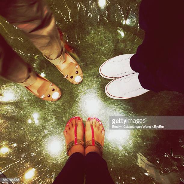 Low Section Of Friends Standing On Glass Floor