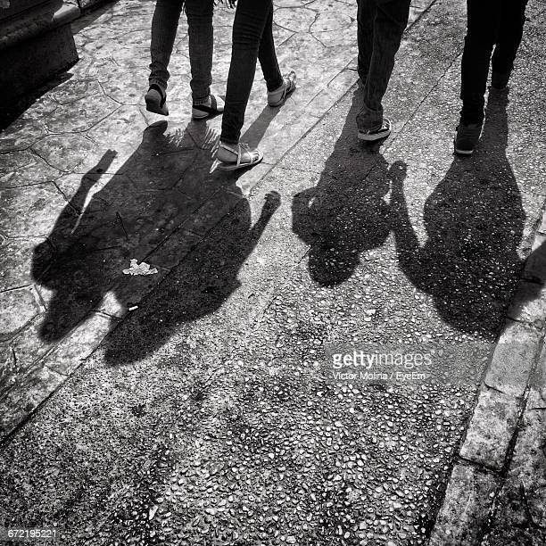 Low Section Of Friends Walking With Shadow On Footpath