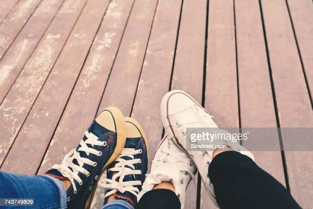 Low Section Of Friends Wearing Canvas Shoes On Boardwalk