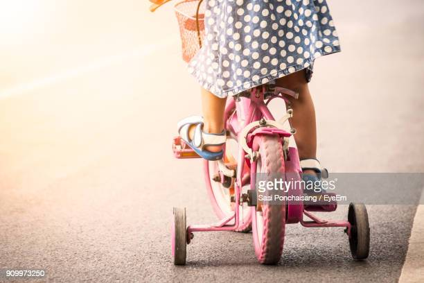 low section of girl cycling on road - wheel stock pictures, royalty-free photos & images