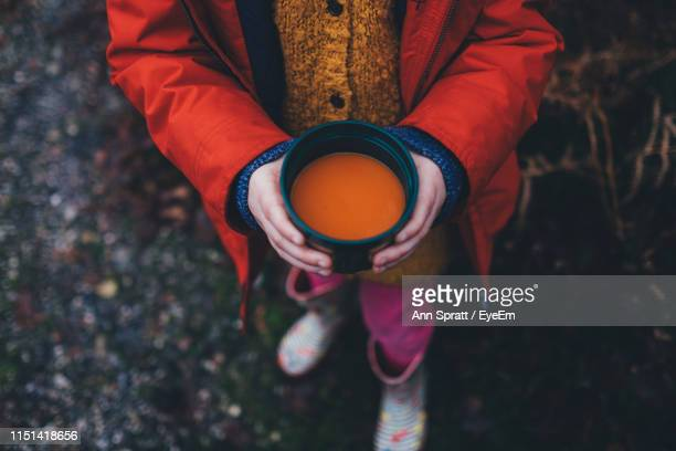 low section of girl holding drink in container - soup stock pictures, royalty-free photos & images
