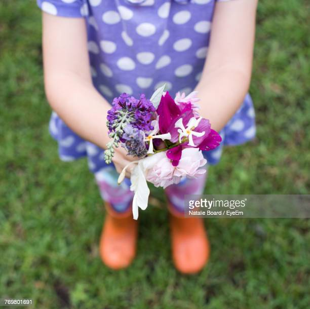 Low Section Of Girl Holding Flowers