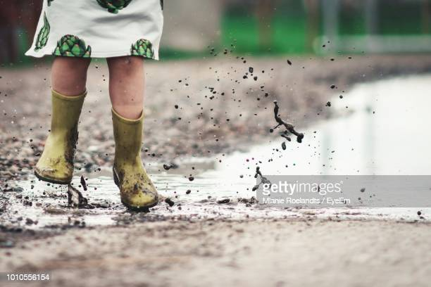 low section of girl jumping in puddle on road - puddle stock pictures, royalty-free photos & images