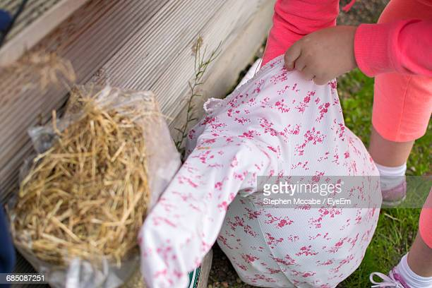 low section of girl making scarecrow - scarecrow agricultural equipment stock photos and pictures