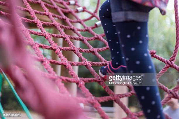 low section of girl on rope in park - ジャングルジム ストックフォトと画像