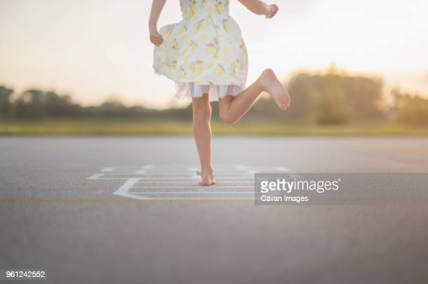 low section of girl playing hopscotch on footpath against sky - hopscotch stock pictures, royalty-free photos & images