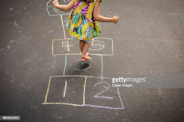 low section of girl playing hopscotch on road - hopscotch stock pictures, royalty-free photos & images