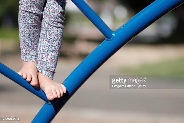 low section of girl playing in playground - ジャングルジム ストックフォトと画像