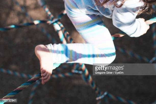 low section of girl playing on jungle gym - ジャングルジム ストックフォトと画像