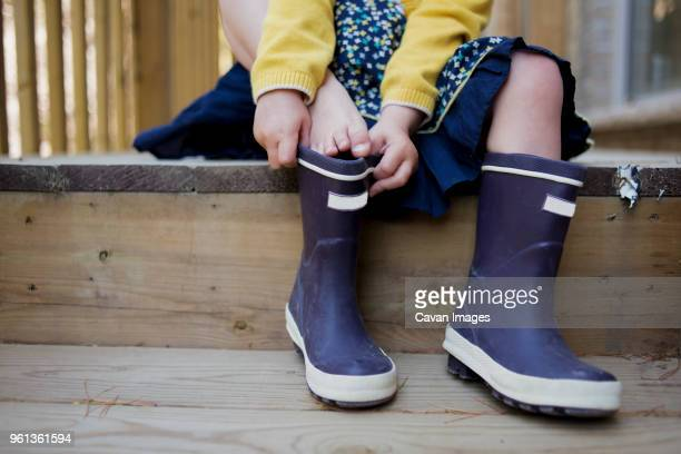 low section of girl putting on rubber boots - stiefel stock-fotos und bilder