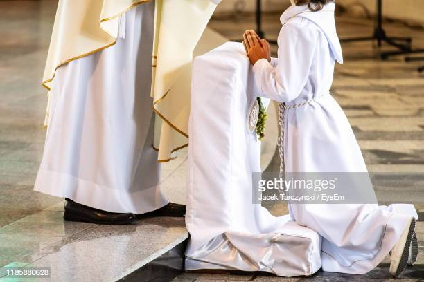 low section of girl receiving communion from priest in church - catolicismo - fotografias e filmes do acervo