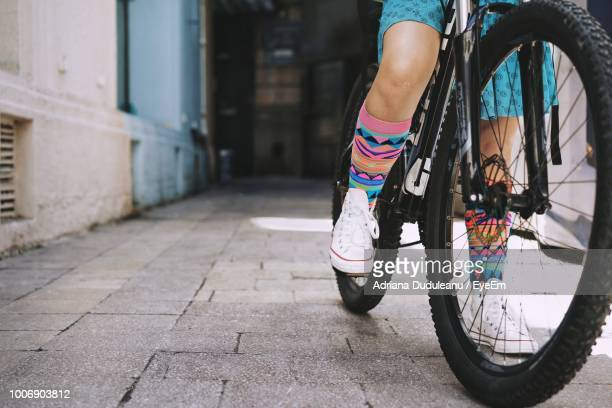 Low Section Of Girl Riding Bicycle On Street