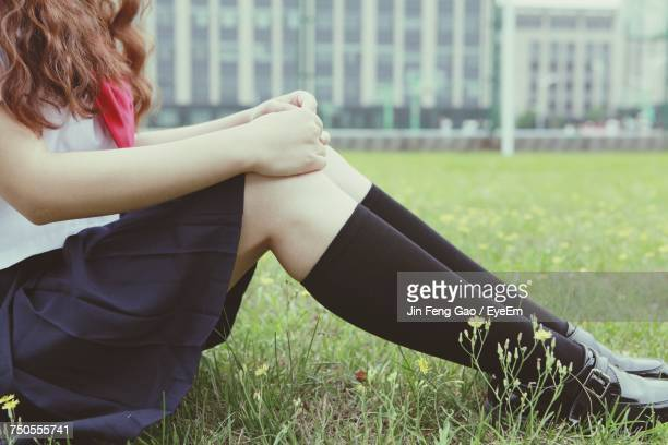 Low Section Of Girl Sitting On Grass
