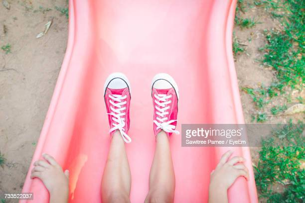 Low Section Of Girl Sitting On Slide At Park