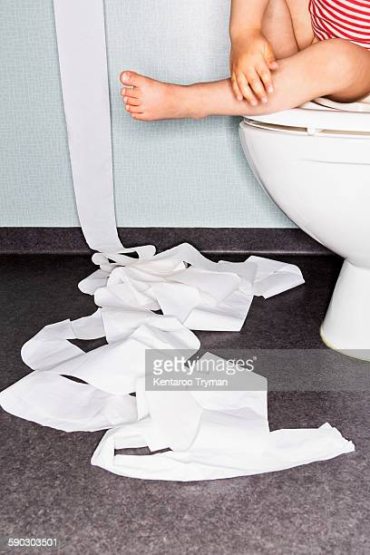 Low section of girl sitting on toilet bowl with paper on floor