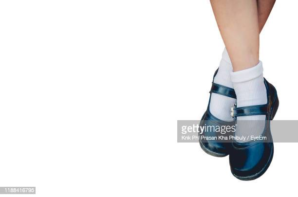 low section of girl standing against white background - school girl shoes stock pictures, royalty-free photos & images