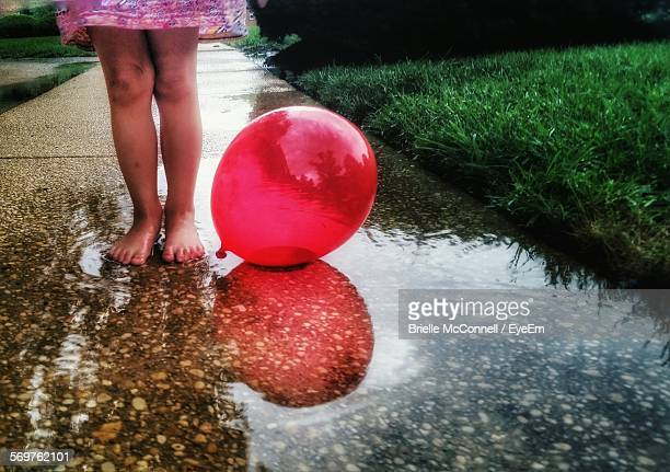 Low Section Of Girl Standing By Balloon In Puddle On Footpath