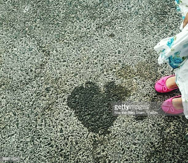 Low Section Of Girl Standing By Heart Shape On Footpath