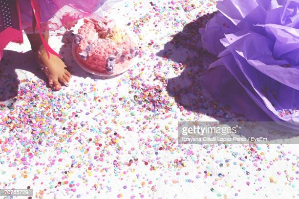 low section of girl standing by messy birthday cake on floor - konfetti boden stock-fotos und bilder