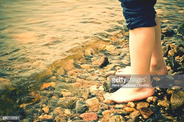 Low Section Of Girl Standing On Pebbles On River