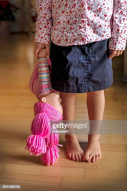 Low section of girl standing on wooden floor holding a doll
