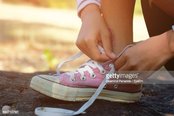low section of girl tying shoelace - children only stock pictures, royalty-free photos & images
